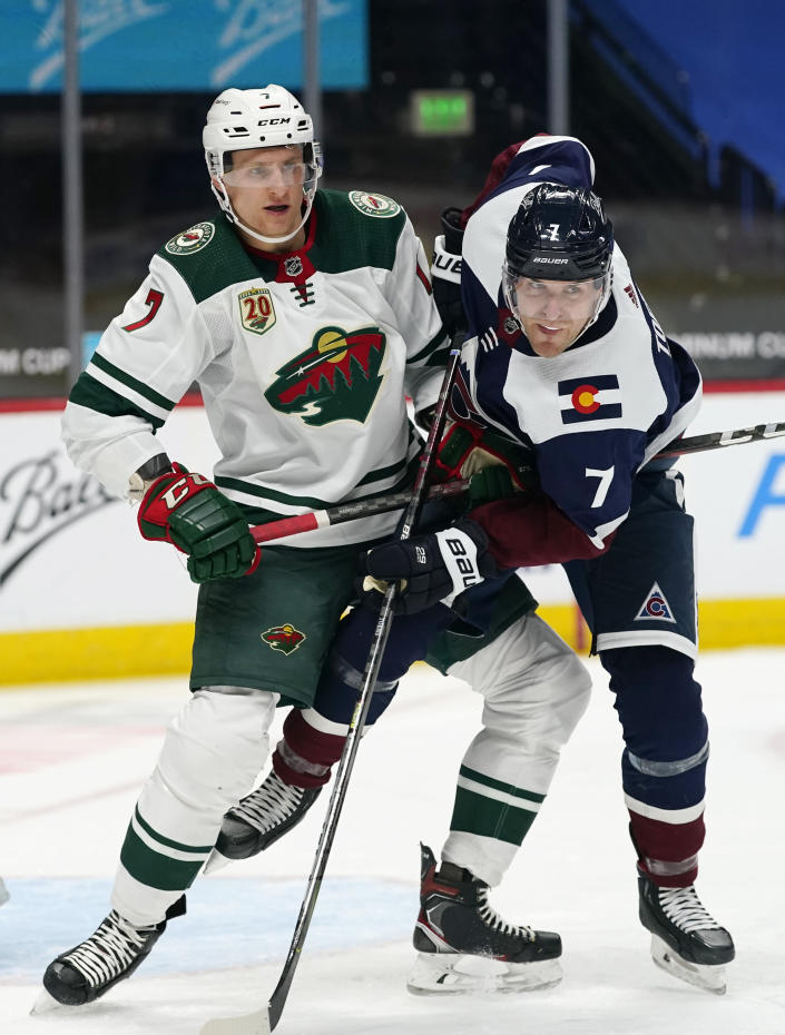 Minnesota Wild center Nico Sturm, left, and Colorado Avalanche defenseman Devon Toews get tangled up while fighting for position in front of the net in the second period of an NHL hockey game Saturday, March 20, 2021, in Denver. (AP Photo/David Zalubowski)