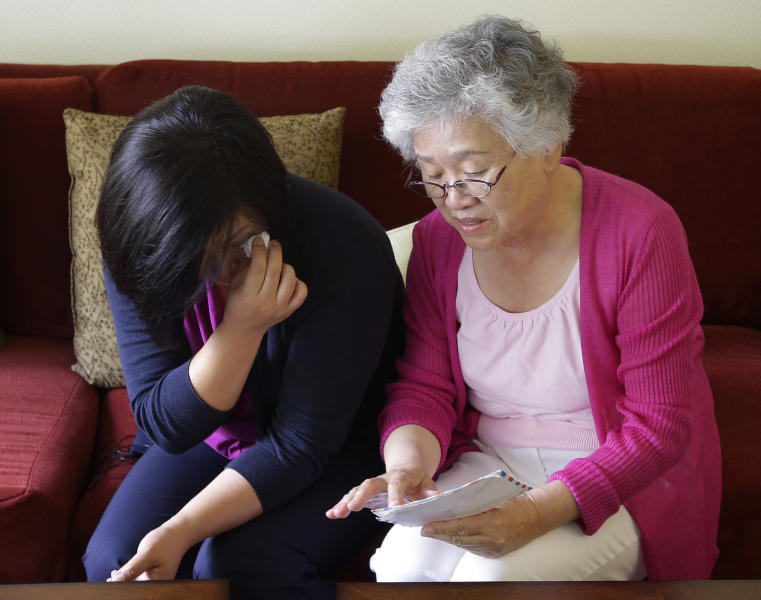 Terri Chung, left, and her mother, Myunghee Bae, right, look at a letter sent from their brother and son, Kenneth Bae, as they sit in Bae's home Wednesday, Aug. 7, 2013, in Lynnwood, Wash. Kenneth Bae, an American tour operator and Christian missionary, has been detained in North Korea since being arrested in November, 2012, and his family is renewing calls for his release as concerns about his health increase. (AP Photo/Ted S. Warren)