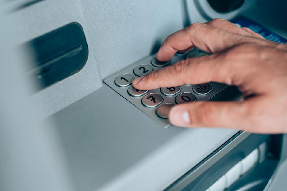 Close-up shot of man's hand withdrawing cash from ATM putting PIN entry