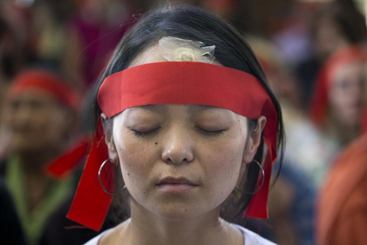 <p>An exile Tibetan wears a ceremonial ribbon as she listens to her spiritual leader the Dalai Lama at Tsuglakhang temple in Dharmsala, India, Saturday, May 27, 2017. The Tibetan leader gave a talk and conducted rituals for an initiation ceremony. (AP Photo/Ashwini Bhatia) </p>