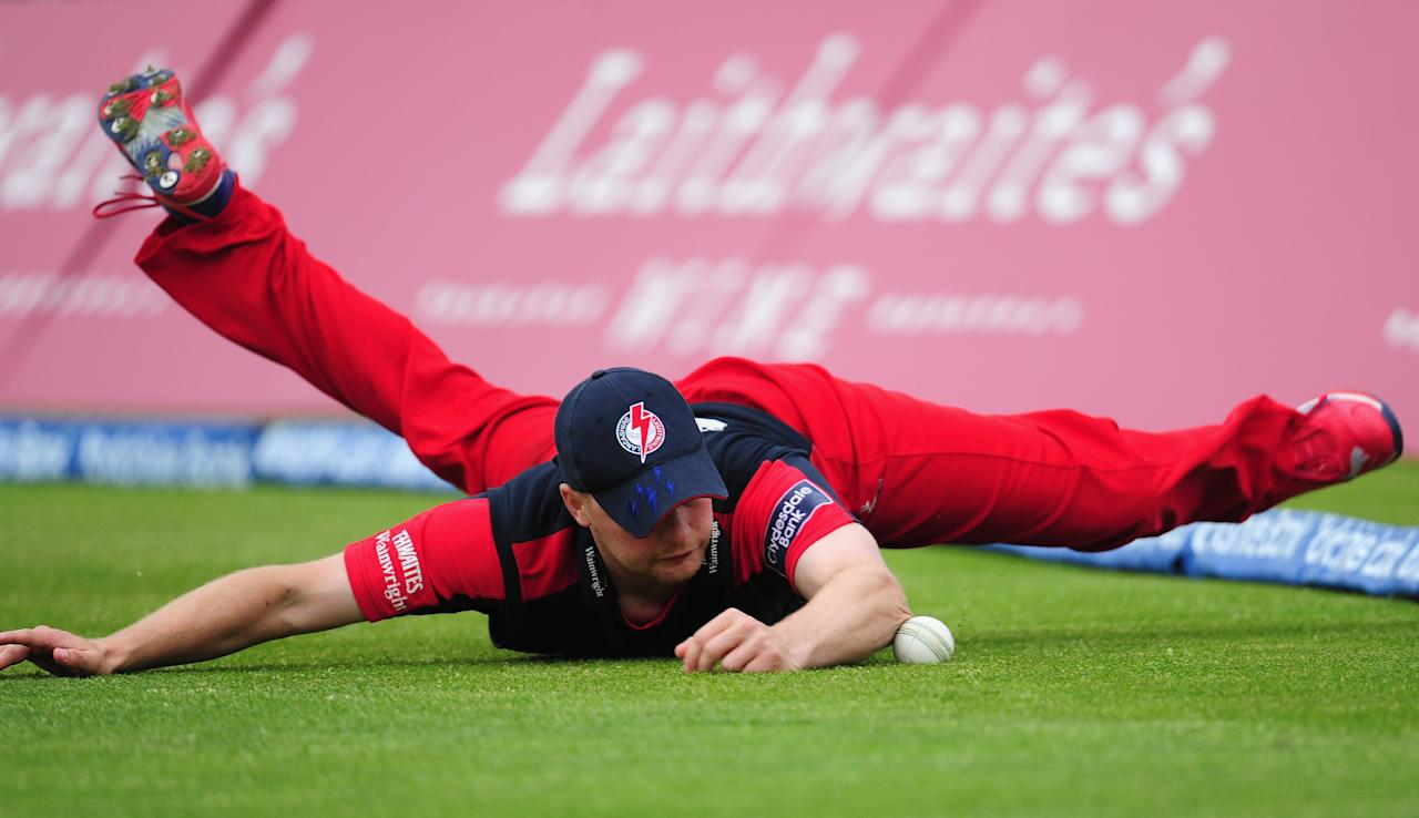 MANCHESTER, ENGLAND - JUNE 05:  Lancashire fielder Karl Brown dives to stop the ball and a certain  boundary during the Clydesdale Bank Pro40 match between Lancashire and Worcestershire at Old Trafford on June 5, 2012 in Manchester, England.  (Photo by Stu Forster/Getty Images)