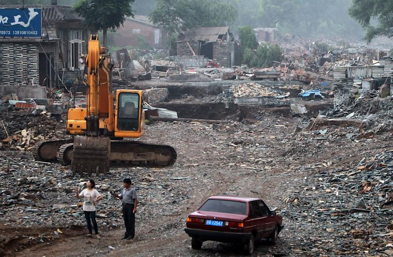 In this photo taken on Wednesday, July 25, 2012, People look at the houses damaged by floods in Fangshan district in Beijing, China. Chinese authorities on Thursday raised Beijing storm's death toll to 77 after the public questioned the days-old tally of 37, with some residents even compiling their own totals in a reflection of deep mistrust of the government's handling of the disaster. (AP Photo) CHINA OUT