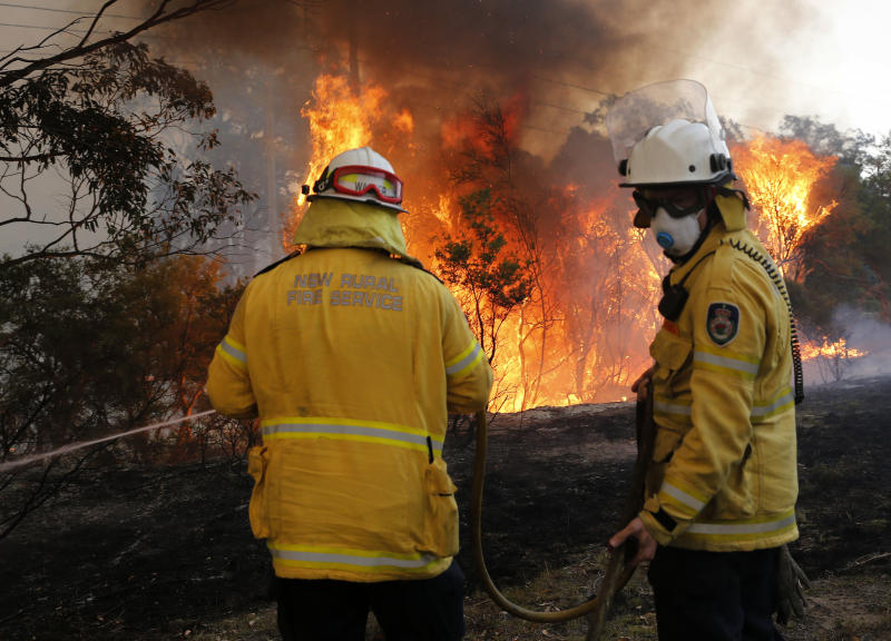 Firefighters try to contain an out of control fire near properties at Avery's lane, near Stanford Merthyr, west of Newcastle.