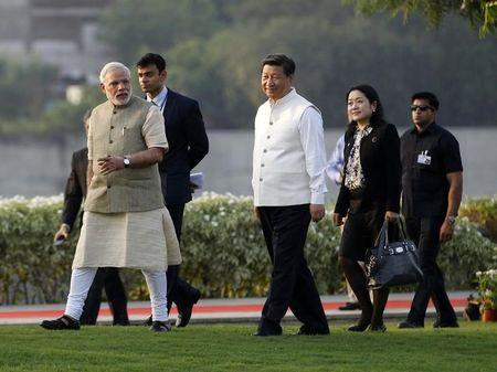 China's President Xi Jinping (C) walks with India's Prime Minister Narendra Modi (L) during his visit to the Sabarmati river front in Ahmedabad September 17, 2014. REUTERS/Amit Dave