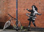 File photo dated 15/10/20 of graffiti artwork, which has been confirmed as the work of street artist Banksy. The artwork, on a side of a property at Rothesay Avenue and Ilkeston Road, Nottingham, depicts a young girl playing with a tyre and is painted on a wall near to an abandoned bicycle that is missing a wheel.