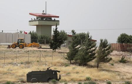 FILE PHOTO: Turkish soldiers stand on a watchtower at the Atmeh crossing on the Syrian-Turkish border, as seen from the Syrian side, in Idlib governorate, Syria