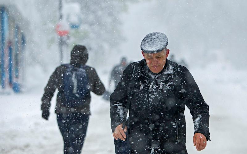 Man walking in snow - Credit: EPA