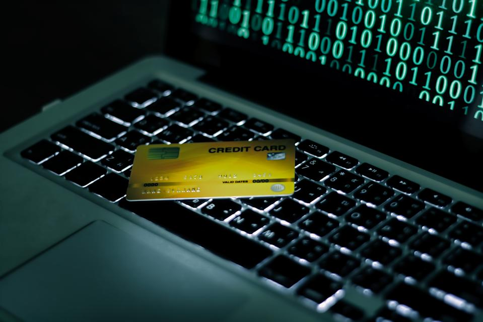 Credit Cards Theft Concept. Hacker with Credit Cards on His Laptop Using Them For Unauthorized Shopping. Photo: Getty