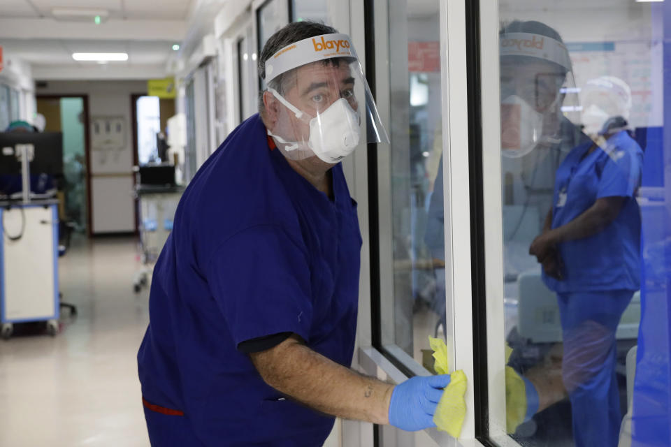 Housekeeper Glen Hayward cleans on the COVID-19 Cotton ward at King's College Hospital in London, Wednesday, Jan. 27, 2021. The scale of Britain's coronavirus outbreak can seem overwhelming, with tens of thousands of new infections and more than 1,000 deaths added each day. But on hospitals' COVID-19 wards, the pandemic feels both epic and intimate, as staff fight the virus one patient at a time, and with no end in sight. (AP Photo/Kirsty Wigglesworth, Pool)