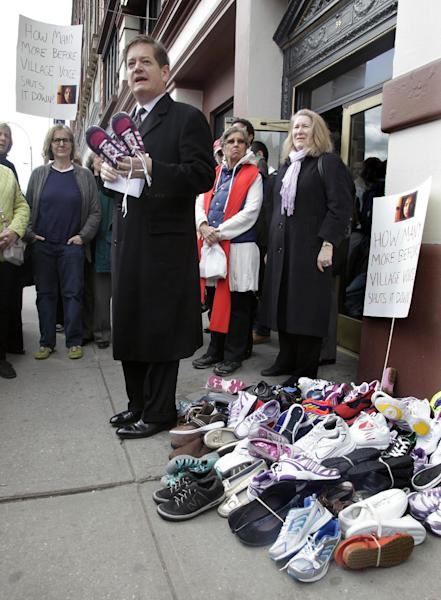 Rev. Galen Guengerich holds a child's shoes and stands next to a stack used as a symbol for child sex trafficking, as he speaks during a protest rally outside the Village Voice on Thursday, March 29, 2012 in New York. A coalition of religious and civic leaders demanded that the Village Voice stop running their adult classified section. The protesters say the section is being used by sex traffickers peddling underage prostitutes. (AP Photo/Bebeto Matthews)