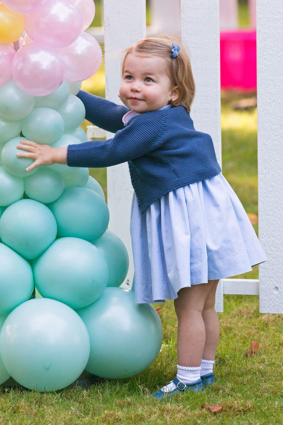 <p>Princess Charlotte strikes a pose with some colorful balloons.</p>