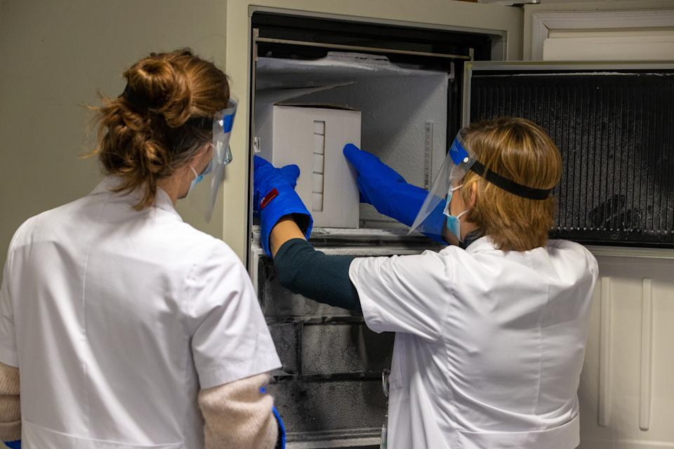 White box of Pfizer-BioNTech vaccines being placed in a freezer by two gloved scientists in lab coats