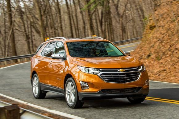 An orange Chevrolet Equinox, a compact crossover SUV, on a mountain road.