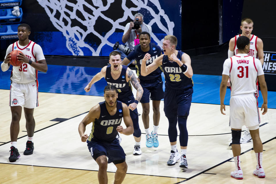 Oral Roberts players celebrate after beating Ohio State in a first-round game in the NCAA men's college basketball tournament, Friday, March 19, 2021, at Mackey Arena in West Lafayette, Ind. (AP Photo/Robert Franklin)