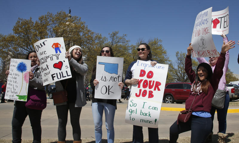 Elementary school teachers in the Putnam City school district of Oklahoma City wave signs at passing cars this week outside the state capitol. (AP)