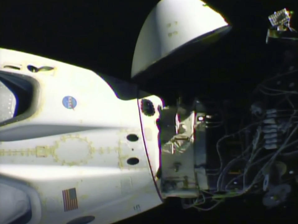 This image from video made available by NASA shows the SpaceX Crew Dragon capsule, left, before it undocks from the International Space Station on Saturday, Aug. 1, 2020. (NASA via AP)