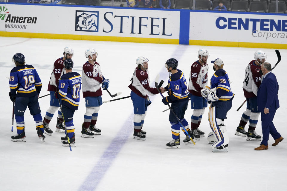 Members of the Colorado Avalanche and St. Louis Blues shake hands following Game 4 of an NHL hockey Stanley Cup first-round playoff series Sunday, May 23, 2021, in St. Louis. Colorado won the game 5-2 to take the series 4-0. (AP Photo/Jeff Roberson)
