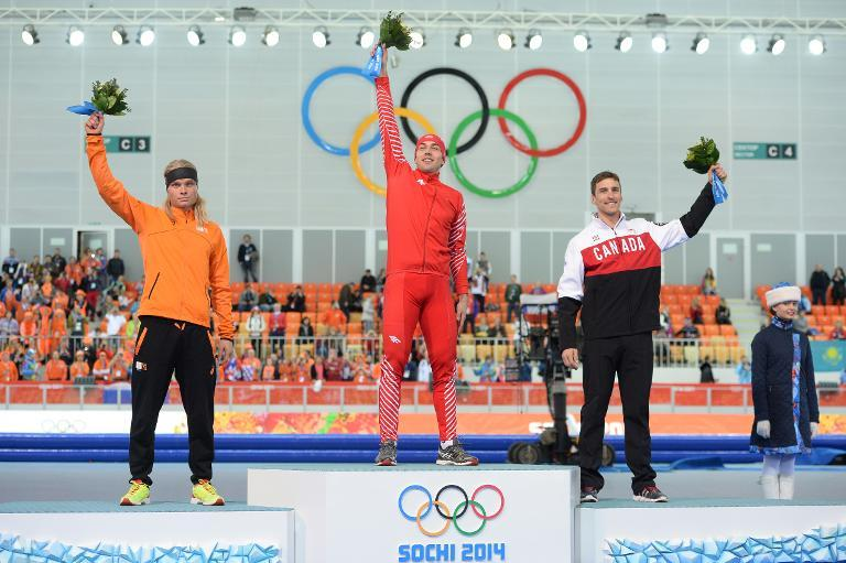 L-R: Netherlands' silver medalist Koen Verweij, Poland's gold medalist Zbigniew Brodka and Canada's bronze medalist Denny Morrison pose on the podium during the Men's Speed Skating 1500m Flower Ceremony on February 15, 2014