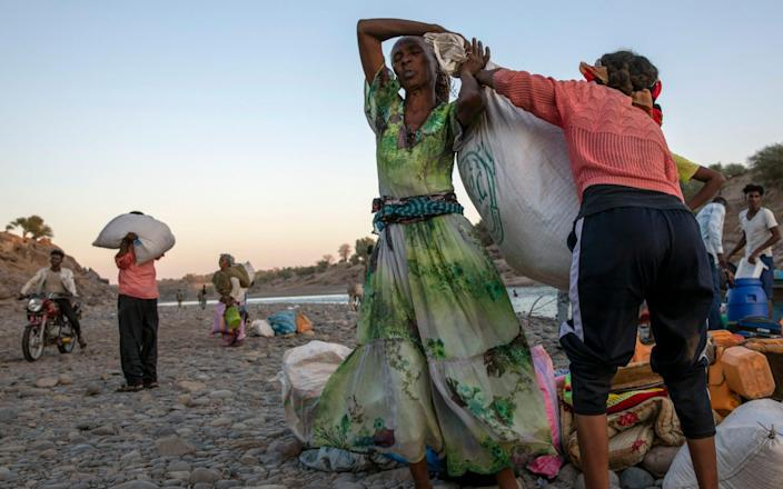 Tigray refugee women help each other carry their belongings after they arrive on the banks of the Tekeze River on the Sudan-Ethiopia border, in Hamdayet - Nariman El-Mofty/AP
