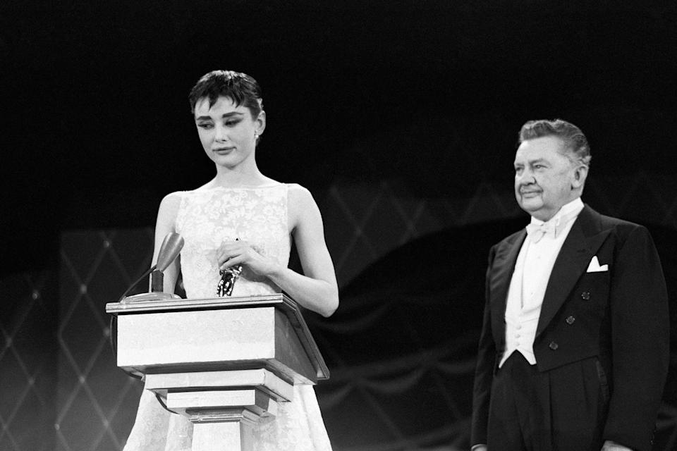 "<p><a href=""https://www.goodhousekeeping.com/life/entertainment/g3793/44-audrey-hepburn-glamorous-photos/"" rel=""nofollow noopener"" target=""_blank"" data-ylk=""slk:Audrey Hepburn"" class=""link rapid-noclick-resp"">Audrey Hepburn</a> took the stage to accept the Best Actress Oscar for her role in <em><a href=""https://www.amazon.com/dp/B000MYFILK?ref=sr_1_1_acs_kn_imdb_pa_dp&qid=1547578076&sr=1-1-acs&autoplay=0&tag=syn-yahoo-20&ascsubtag=%5Bartid%7C10055.g.5132%5Bsrc%7Cyahoo-us"" rel=""nofollow noopener"" target=""_blank"" data-ylk=""slk:Roman Holiday"" class=""link rapid-noclick-resp"">Roman Holiday</a></em><em><em>.</em></em></p>"