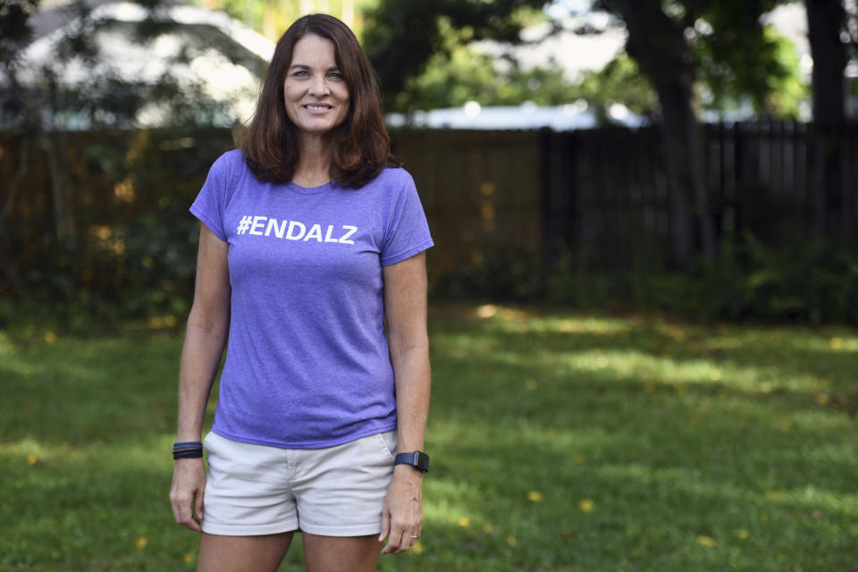 """Michele Hall stands in her backyard Thursday, June 24, 2021, in Bradenton, Fla. Hall, 54, diagnosed with early Alzheimer's last year, calls the new drug Aduhelm """"the first tiny glimmer of hope"""" she'll get more quality time with her husband and their three adult children. (AP Photo/Steve Nesius)"""