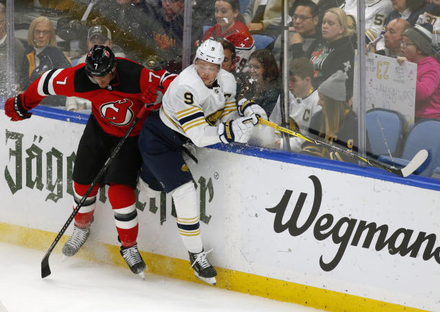 Buffalo Sabres forward Jack Eichel (9) and New Jersey Devils defenseman Matt Tennyson (7) collide during the first period of an NHL hockey game Monday, Dec. 2, 2019, in Buffalo, N.Y. (AP Photo/Jeffrey T. Barnes)