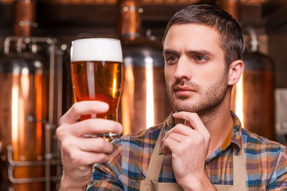 A brewer carefully examining a pint of beer being held up in his right hand.