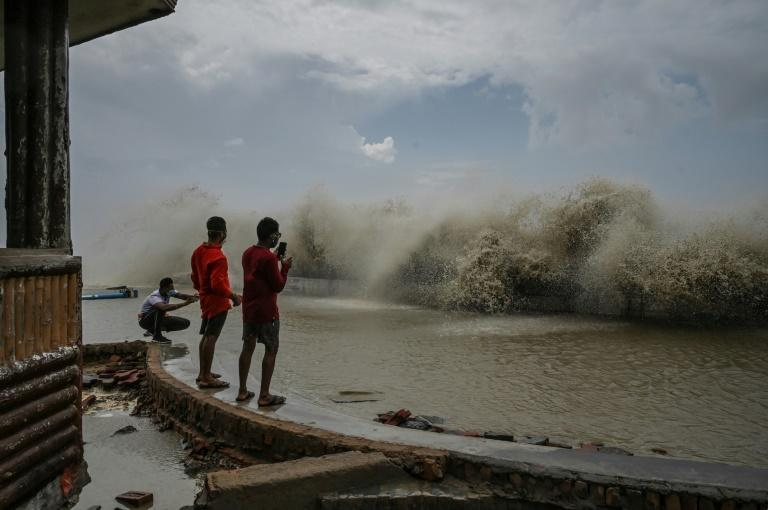 Residents take pictures of waves lashing a shoreline after Cyclone Yaas hit India's eastern coast in the Bay of Bengal in Digha, about 190 kilometres from Kolkata