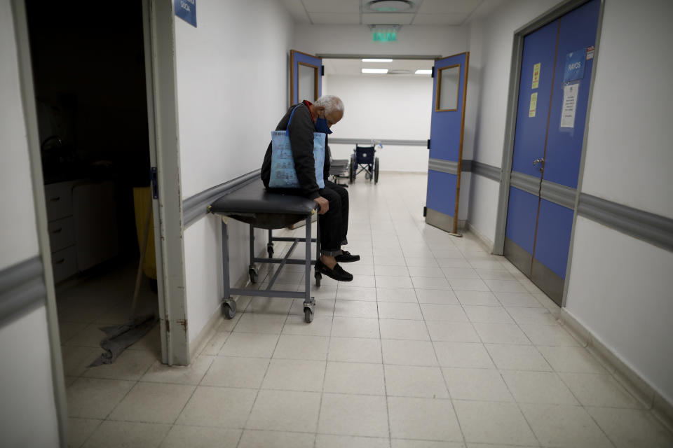 A man sits in a corridor as he waits for news of his wife who is a suspected COVID-19 case at Llavallol Dr. Norberto Raúl Piacentini Hospital in Lomas de Zamora, Argentina, Saturday, May 1, 2021. The man's wife was intubated and a few days later passed away. (AP Photo/Natacha Pisarenko)