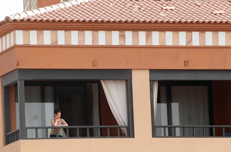 A woman looks from a terrace of H10 Hotel, which is on lockdown after novel coronavirus has been confirmed in Adeje, on the Spanish island of Tenerife, Spain.
