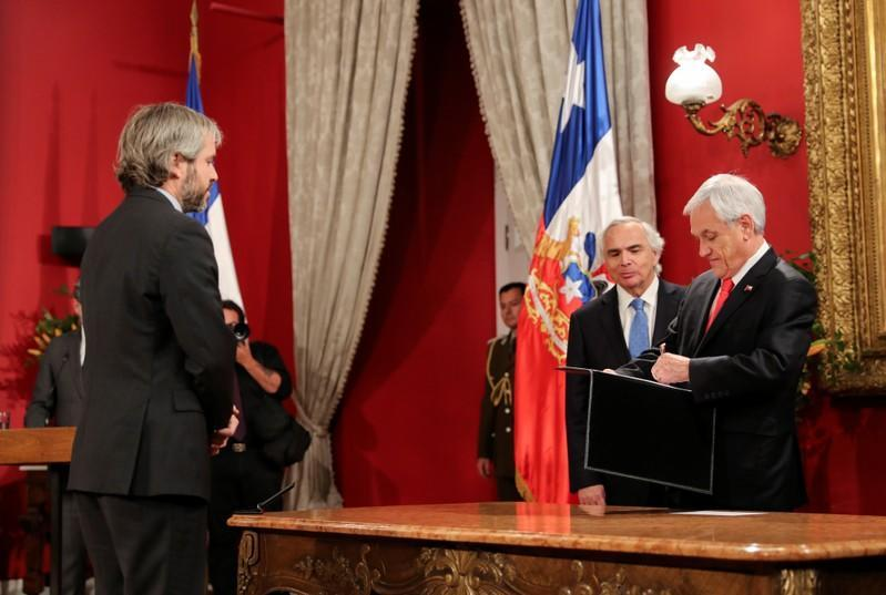 Chile's newly appointed Interior Minister Gonzalo Blumel looks on as Chilean President Pinera signs a document next to former minister Chadwick during a cabinet reshuffle at the government house in Santiago