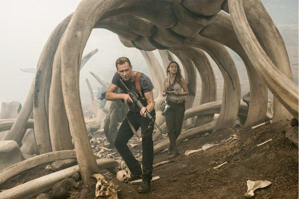Two people, one with a gun raised and one with a camera search under dinosaur bones.