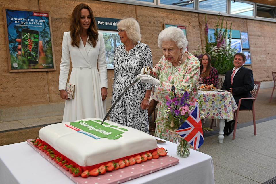 ST AUSTELL, ENGLAND - JUNE 11: Queen Elizabeth II (C) attempts to cut a cake with a sword, lent to her by The Lord-Lieutenant of Cornwall, Edward Bolitho, to celebrate of The Big Lunch initiative at The Eden Project during the G7 Summit on June 11, 2021 in St Austell, Cornwall, England. UK Prime Minister, Boris Johnson, hosts leaders from the USA, Japan, Germany, France, Italy and Canada at the G7 Summit. This year the UK has invited India, South Africa, and South Korea to attend the Leaders' Summit as guest countries as well as the EU. (Photo by Oli Scarff - WPA Pool / Getty Images)