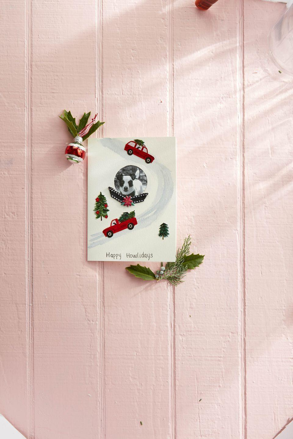"""<p>Send love from your furry family member this year with this easy DIY photo card. </p><p><strong>To make:</strong> Cut a small round hole in the front of a plain greeting card. Glue a picture to the inside of the card so that it is centered in the opening (you can glue a piece of corresponding color paper over the back of the picture to create a clean finish, if desired). Use a light gray watercolor marker to draw a snowy road around the picture. Cut out trees, cars, and truck from holiday-themed wrapping paper and glue to the card. Attach a short length of ribbon and additional wrapping paper decoration just below the picture.</p><p><a class=""""link rapid-noclick-resp"""" href=""""https://www.amazon.com/American-Greetings-Reversible-Christmas-Wrapping/dp/B07V9YTYRH/ref=sr_1_6?tag=syn-yahoo-20&ascsubtag=%5Bartid%7C10050.g.3872%5Bsrc%7Cyahoo-us"""" rel=""""nofollow noopener"""" target=""""_blank"""" data-ylk=""""slk:SHOP WRAPPING PAPER"""">SHOP WRAPPING PAPER</a></p>"""