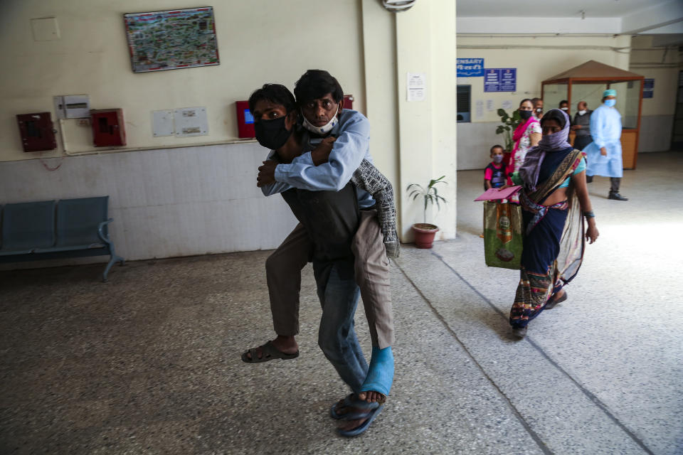 A man carries another on his back as he brings him for medical check up at a government hospital in Jammu, India, Monday, June 21, 2021. (AP Photo/Channi Anand)