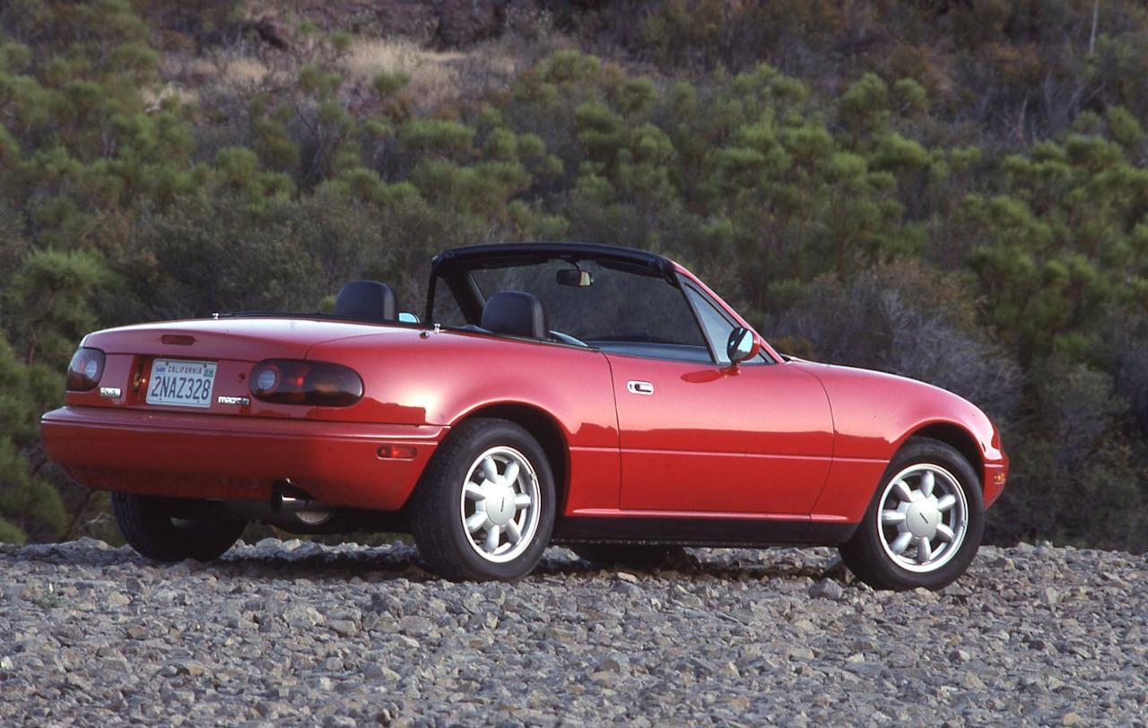 """<p>The original Miata, which comes to be known as the NA generation, is officially released as a 1990 model and vaguely resembles a '60s-era Lotus Elan remastered for the 20th century. Its features are endearing, including pop-up headlights that, when opened, give the MX-5 the appearance of a happy, wide-eyed thing-especially in conjunction with the rounded """"mouth"""" in the bumper<br></p>"""