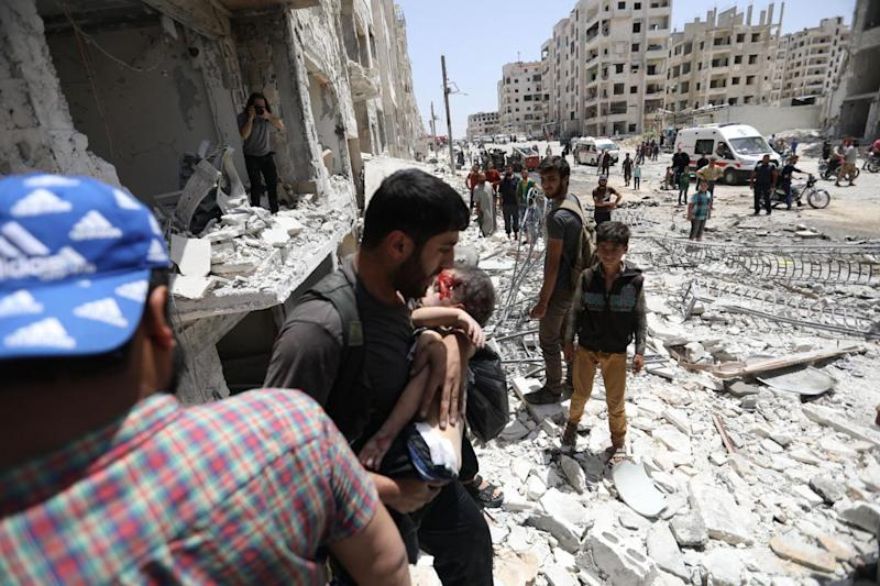 A man carries a wounded child after a car bombing in Idlib in May. The city has been devastated by siege, leading to international calls for a ceasefire to prevent a humanitarian crisis. Russia has granted rebels an ultimatum to leave the city or face further conflict. (AFP/Getty/Omar Haj Kadour)