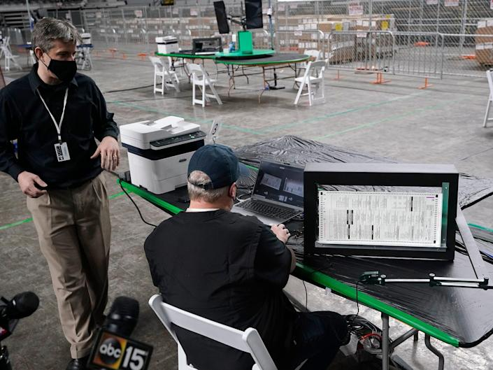 Cyber Ninjas owner Doug Logan, left, a Florida-based consultancy, talks about overseeing a 2020 election ballot audit ordered by the Republican lead Arizona Senate at the Arizona Veterans Memorial Coliseum.