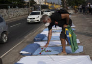 A demonstrator places roses on mattresses symbolizing COVID-19 victims, during a protest against the Government's handling of the COVID-19 pandemic, organized by the Rio de Paz NGO, in front of the Ronaldo Gazolla hospital in Rio de Janeiro, Brazil, Wednesday, March 24, 2021. (AP Photo/Silvia Izquierdo)