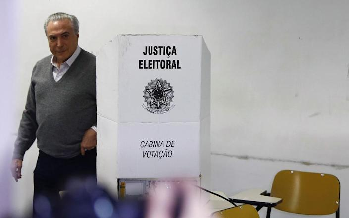 Brazilian President Michel Temer abruptly changed his schedule to vote two hours earlier than previously announced, getting into the polling station before doors even opened to the public (AFP Photo/Miguel Schincariol)