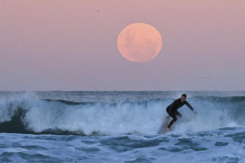 """<p>SYDNEY, AUSTRALIA - MAY 26: A surfer is seen as the """"Super Flower Blood Moon"""" rises over the Pacific Ocean at Bondi Beach in Sydney, Australia on May 26, 2021. The """"Super"""" moon observed in May is often defined as """"flower moon"""" as well, mainly due to association with flowers blooming at this time of year. During the eclipse, the moon turns into a deep blood-red color, known as """"blood moon."""" This celestial incident -- known as """"Super Flower Blood Moon"""" -- is the only full lunar eclipse of this year. (Photo by Steven Saphore/Anadolu Agency via Getty Images)</p>"""