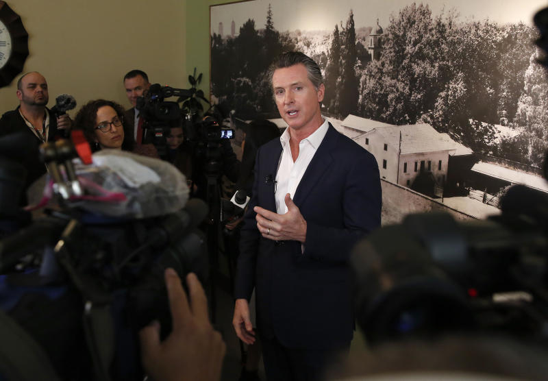 In this photo taken Tuesday, March 26, 2019, Gov. Gavin Newsom talks with reporters in Sacramento, Calif. Newsom, on Thursday, March 28, says PG&E plans to remake its board of directors with hedge fund financiers and people who have little experience in utility operations and safety. Putting hedge fund managers in charge of the company, said Newsom, will send a message the utility prioritizes profits over providing safe and reliable energy service. The utility did not immediately comment. (AP Photo/Rich Pedroncelli)