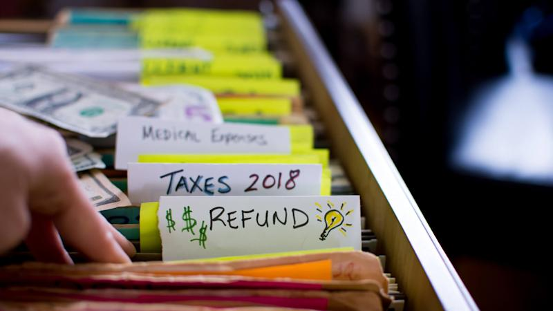 Tax refund conceptual tax season tax preparation photography with files and tax forms in filing cabinet and words refund and taxes 2018 written on file folders with light bulb for ideas and US dollar cash in background.