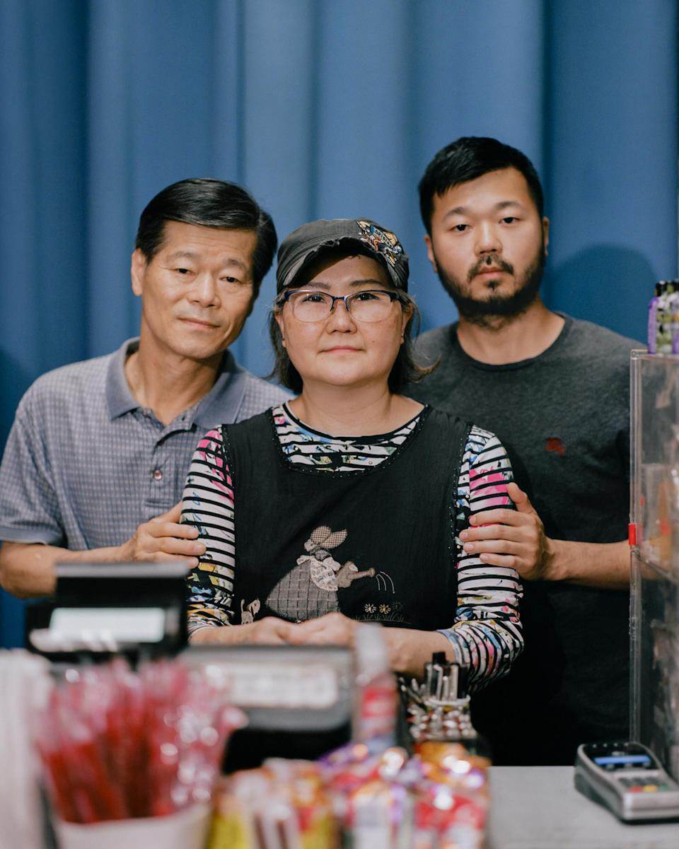 """<strong>'I STILL WISH FOR A BETTER LIFE.' </strong>Mun Sung, left, and Joyce Sung, center, stand with their 35-year-old son Mark Sung, right, in the family's Charlotte, N.C., convenience store on May 29. The elder Sungs watched helplessly on March 30 as a man smashed through glass with a metal pole, ripped down racks and hurled racial slurs at them inside the store they've owned for two decades. Despite facing racism at work on a daily basis since the pandemic began—even growing hardened to the hatred month after month—Mun never expected his family would fall victim to such violence. """"I feel so terribly bad,"""" the 65-year-old says, """"because how can people do that to us?"""" Less than two months later, it happened again. On May 25, after being told he did not have enough money for cigarettes, a customer shouted racial slurs as he pummeled a sheet of plexiglass at the checkout counter until it shattered on Joyce, 63, bruising her forehead. """"Knowing that we're going to get cursed out every day while we're getting ready for work,"""" she says, pausing to think, """"we don't know what words to use."""" The family has few other options. The pandemic drove down sales at the store by about 45%—and all their employees quit over safety concerns—so the Sungs say they don't have the luxury to stop working. Instead, they clock in 13-hour days, seven days a week, and have developed a routine for responding to hate: call the police, assess the damage, file an insurance claim, then go back to work. It's not the life Mun imagined for himself or his family when he left South Korea for the U.S. in 1983. But he and Joyce keep going, in large part to have some money to leave for Mark's two toddlers, their only grandchildren. """"The first time I came to the United States, I had big dreams and high hopes,"""" Mun says. """"I didn't make it, but I still wish for a better life.""""<span class=""""copyright"""">Emanuel Hahn for TIME</span>"""