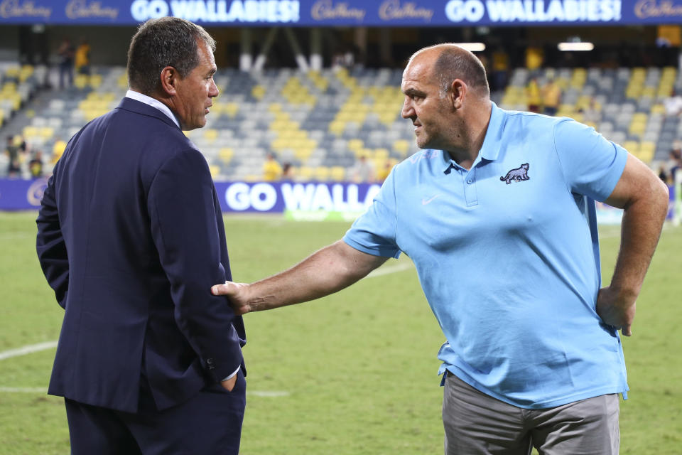 Australia's rugby coach Dave Rennie, left, talks with Argentina's coach Mario Ledesma following the Rugby Championship test match between the Pumas and the Wallabies in Townsville, Australia, Saturday, Sept. 25, 2021. (AP Photo/Tertius Pickard)