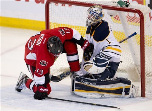 Ottawa Senators center Peter Regin tries to remove his skate from the pads of Buffalo Sabres goalie Jhonas Enroth during the second period of an NHL hockey game Tuesday, Feb. 5, 2013, in Ottawa, Ontario. (AP Photo/The Canadian Press, Adrian Wyld)