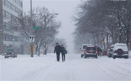 A couple make their way down a snow-covered street, as a winter storm moves across the midwest, in Milwaukee, Wisconsin December, 22, 2013. REUTERS/Darren Hauck