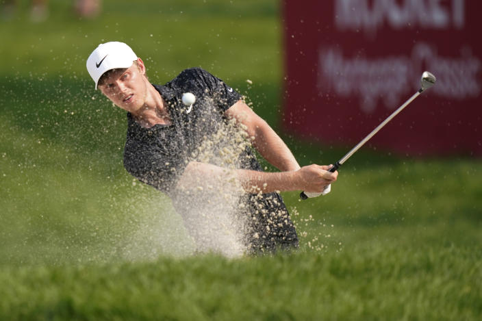Cam Davis of Australia hits from the sand onto the 17th cup for an eagle during the final round of the Rocket Mortgage Classic golf tournament, Sunday, July 4, 2021, at the Detroit Golf Club in Detroit. (AP Photo/Carlos Osorio)