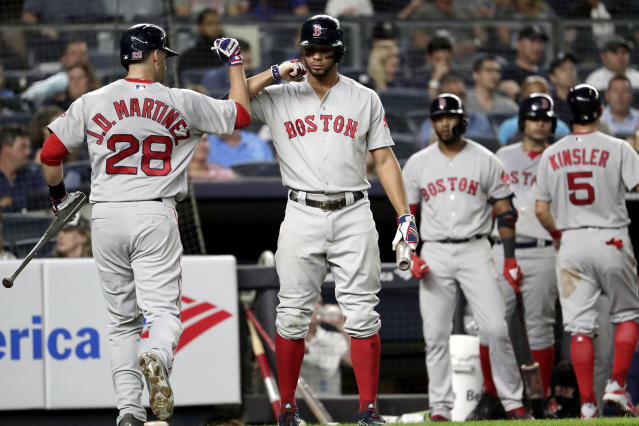 Boston Red Sox's Oscar Hernandez (28) bumps forearms with Xander Bogaerts after Hernandez's sacrifice fly drove in Ian Kinsler, right, during the third inning of a baseball game against the New York Yankees, Tuesday, Sept. 18, 2018, in New York. (AP Photo/Julio Cortez)