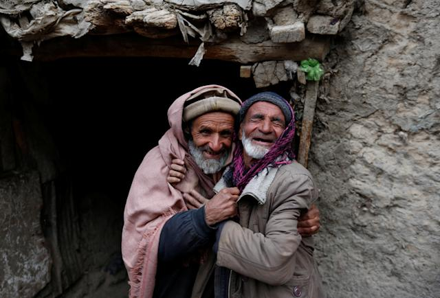 <p>Mirza (R), 65, and Noor Mohammad, 72, pose for a picture at Ka Faroshi bird market in Kabul, Afghanistan, Jan. 18, 2018. (Photo: Mohammad Ismail/Reuters) </p>